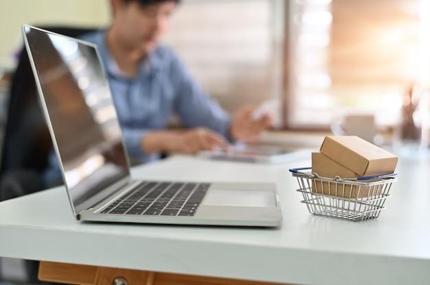 Zakupy online, pudełka w sklepie internetowym na wózkach to forma handlu elektronicznego.