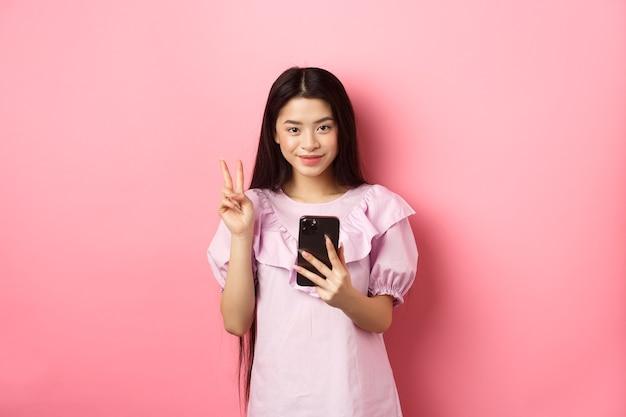 Zakupy online. stylowa azjatycka nastolatka za pomocą smartfona, pokazuje znak pokoju i uśmiecha się zadowolony do kamery, stojąc na różowym tle.