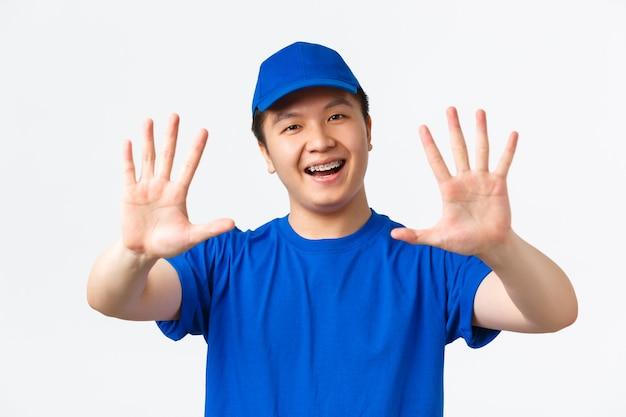 Zakupy online, szybka wysyłka, pracownicy i koncepcja dostawy do domu. pewny siebie, uśmiechnięty kurier azjatycki mężczyzna z szelkami, ubrany w niebieski mundur, pokazujący numer dziesięć, puste czyste ręce, białe tło