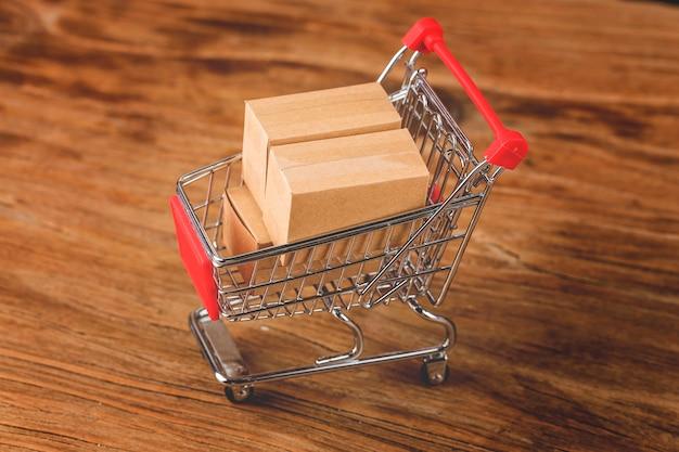 Zakupy online w domu. kartony w koszyku na klawiaturze laptopa