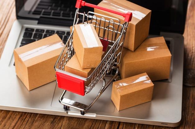 Zakupy online w domu koncepcja. kartony w koszyku na klawiaturze laptopa.