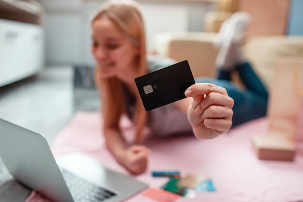 Zakupy online w domu. zbliżenie banku, karta kredytowa pełna pieniędzy do zapłaty w sklepie internetowym