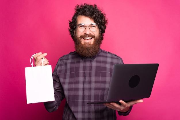 Zakupy online, wesoły brodaty mężczyzna trzyma
