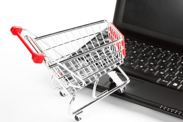 Zakupy online. wózek na zakupy z notatnikiem na bielu.