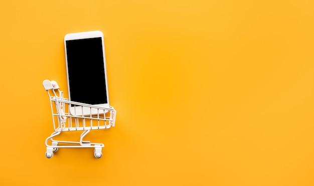 Zakupy online z makietą wózka i smartfona.
