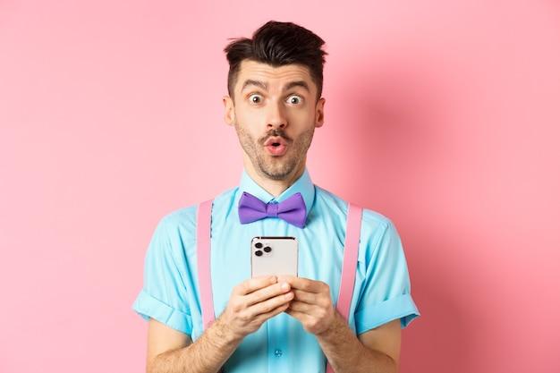 Zakupy online. zaintrygowany facet w muszce, przeglądający internetową ofertę promocyjną na telefonie komórkowym, mówi wow przed kamerą, trzyma smartfon, stoi na różowym tle.