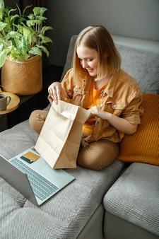 Zakupy online, zamawianie dostawy. nastolatek dziewczyna relaksuje się na kanapie, biorąc pod uwagę zakupy z laptopem. szczęśliwa młoda kobieta robi rozpakowywanie zamówień online towarów lub żywności. makiety papierowych toreb.