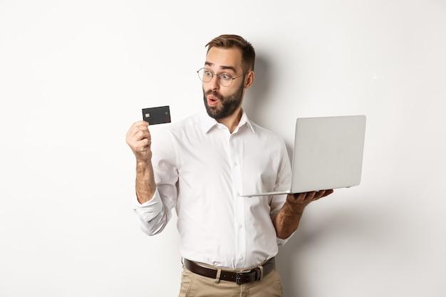 Zakupy online. zdziwiony biznesmen posiadania laptopa, patrząc pod wrażeniem karty kredytowej, stojąc na białym tle.
