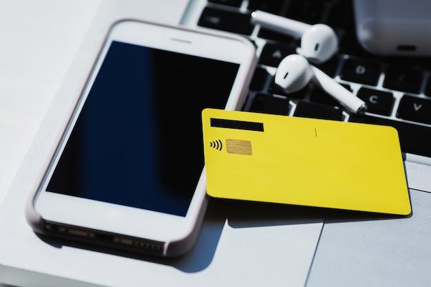 Zakupy online ze zdjęciem z bliska z telefonem komórkowym, smartfonem, słuchawkami i kartą kredytową.