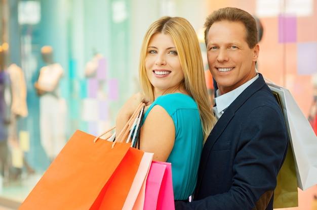 Zakupy para. wesoła dojrzała para trzymająca torby z zakupami i patrząca przez ramię, stojąc w centrum handlowym