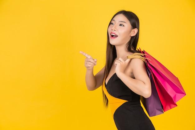 Zakupy piękna kobieta trzyma kolorową papierową torbę na kolorze żółtym.