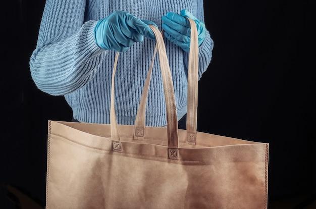 Zakupy podczas pandemii covid-19. kobieta w masce medycznej i rękawiczkach trzyma torbę na zakupy w supermarkecie na czarnej ścianie.