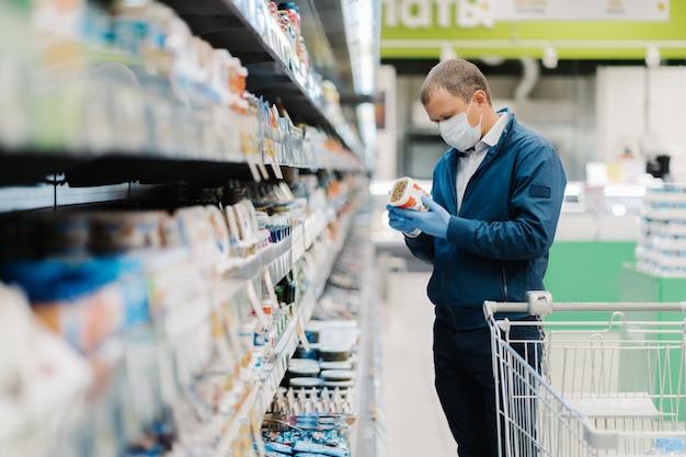 Zakupy podczas pandemii koronawirusa. młody człowiek nosi maskę medyczną, a rękawice ochronne wybiera produkt w sklepie, kupuje produkty niezbędne do pozostania w domu przez długi czas podczas kwarantanny