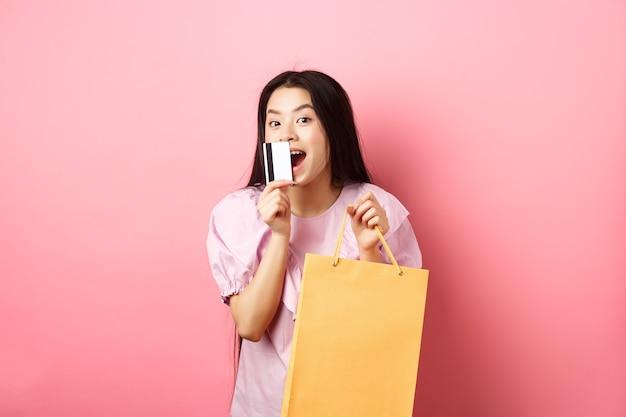 Zakupy. podekscytowana piękna azjatka kupuje w sklepach, trzymając papierową torbę i całując plastikową kartę kredytową, stojąc na różowym tle.
