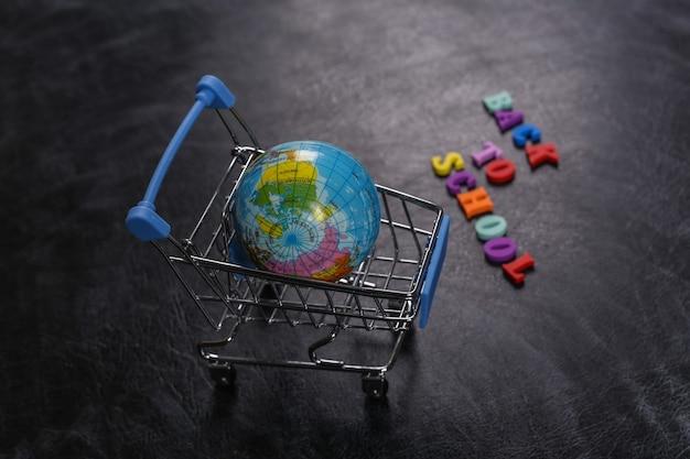 Zakupy przedszkolne. supermarket wózek z kulą ziemską na tablicy kredą z tekstem powrót do szkoły.