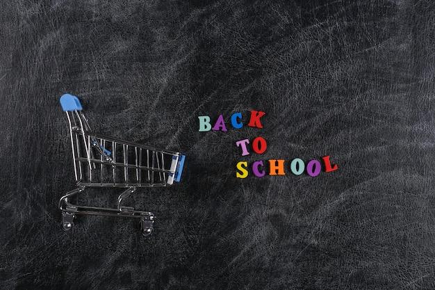 Zakupy przedszkolne. wózek w supermarkecie na tablicy kredowej z tekstem powrót do szkoły.