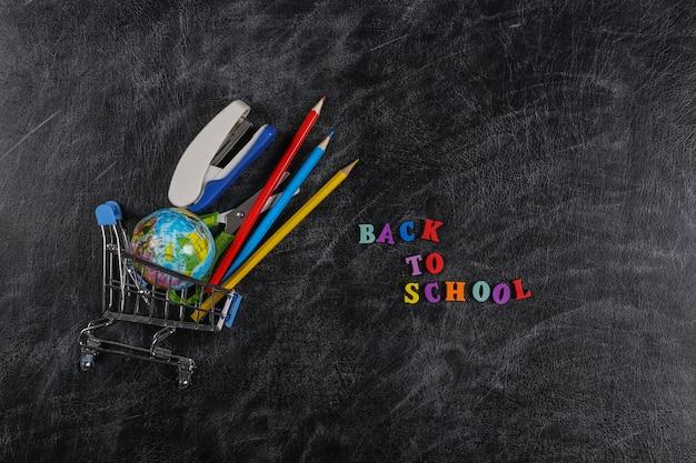 Zakupy przedszkolne. wózek w supermarkecie z przyborami szkolnymi na tablicy kredowej z napisem powrót do szkoły