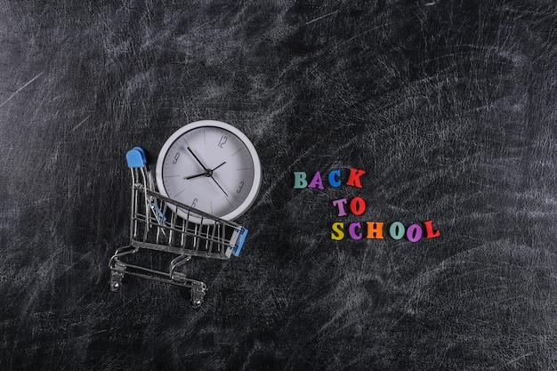 Zakupy przedszkolne. wózek w supermarkecie z zegarem na tablicy kredowej z tekstem powrót do szkoły.