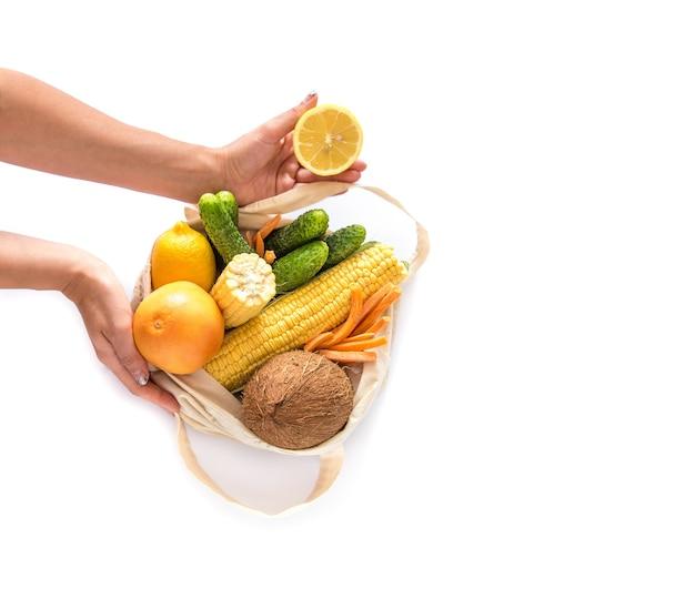 Zakupy spożywcze z eko torbą na białej ścianie rękami. koncepcja braku odpadów i plastiku. leżał na płasko. skopiuj miejsce.
