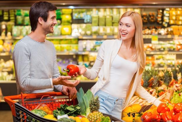 Zakupy to świetna zabawa. szczęśliwe młode kobiety dające czerwoną paprykę swojemu chłopakowi podczas zakupów w sklepie spożywczym