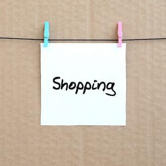 Zakupy. uwaga jest napisana na białej naklejce, która wisi za pomocą spinacza