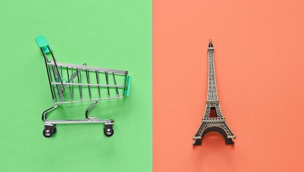 Zakupy w minimalistycznej koncepcji paryża. wózek sklepowy, figurka wieży eiffla na pastelowym kolorowym tle. widok z góry