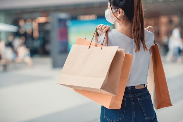 Zakupy w okresie poczęcia kwarantanny, kobieta ubrana w maskę ochronną trzymając papierowe torby.