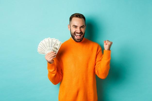 Zakupy. wesoły facet trzyma pieniądze, wygrywa nagrodę w gotówce i robi pompkę pięścią, triumfuje