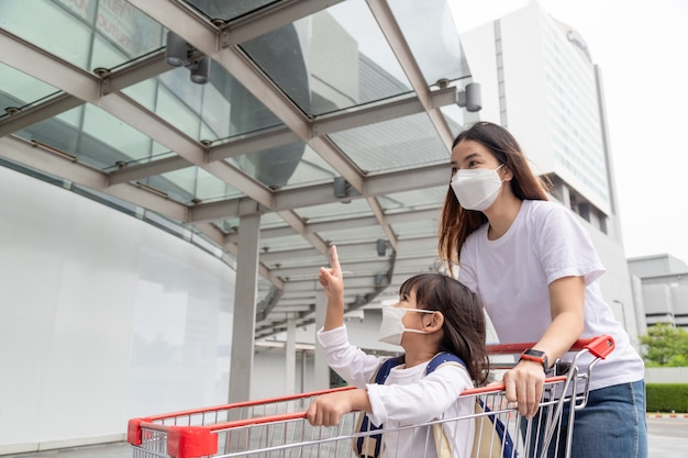 Zakupy z dziećmi podczas epidemii wirusa. asian matka i córka w masce chirurgicznej w supermarkecie.