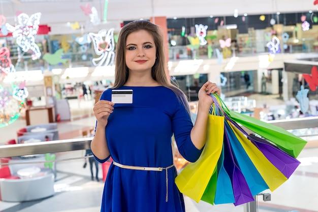 Zakupy z kartą kredytową, kobieta z torbami w centrum handlowym