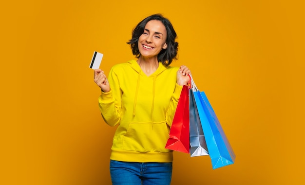 Zakupy za pomocą karty kredytowej. wesoła dziewczyna ubrana w żółtą bluzę z kapturem, trzymająca w jednej ręce kartę kredytową, aw drugiej kolorowe torebki z zakupami.