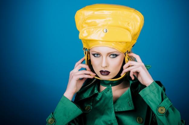 Zakupy, zniżki, sprzedaż, koncepcja stylu - modna kobieta z idealnym makijażem w zielonej kurtce z kobiecą torbą na głowie. pani w zielonym płaszczu trzyma za paskiem stylową modną żółtą torebkę. skopiuj miejsce