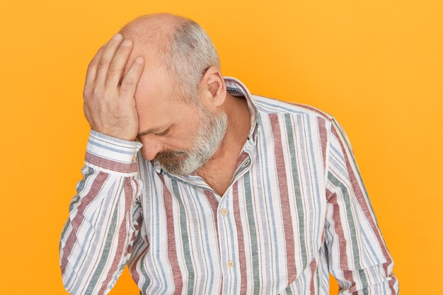 Żal, smutek, stres i depresja. studio strzał przygnębionego, nieszczęśliwego łysego starszego mężczyzny z grubą brodą trzymającego rękę na głowie, wstydzącego się lub przepraszającego za popełnienie dużego błędu, wyrzutów sumienia