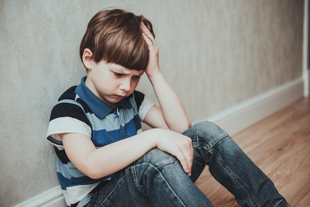 Żal smutnego małego chłopca siedzącego samotnie, zestresowanego przygnębionego dziecka płaczącego z depresją, lękiem, problemami ze zdrowiem psychicznym, samotny chłopiec z ręką na głowie