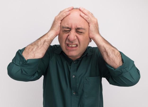 Żal z zamkniętymi oczami mężczyzna w średnim wieku w zielonej koszulce chwycił głowę na białym tle na białej ścianie