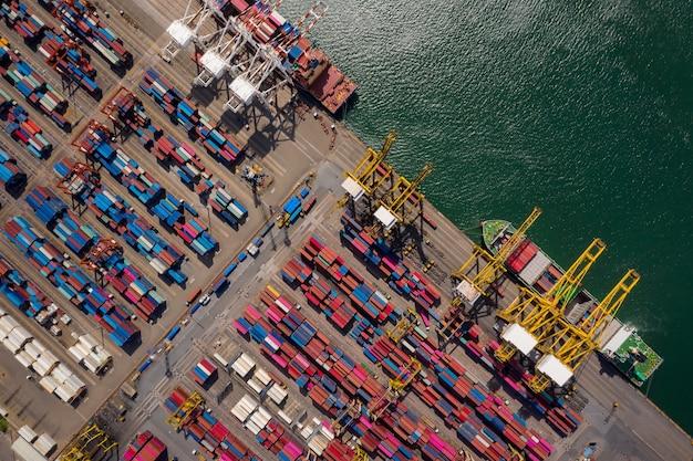Załadunek i rozładunek kontenerowców w porcie morskim, widok z lotu ptaka na logistykę biznesową, import i eksport, transport ładunków statkiem kontenerowym w porcie, załadunek kontenerów statek towarowy,