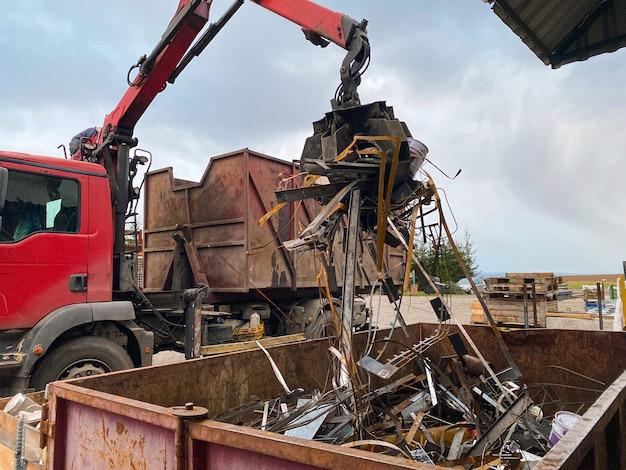 Załadunek złomu na ciężarówkę chwytak dźwigowy ładuje zardzewiały metalowy złom w doku ciężarówka z chwytakiem ładuje złom przemysłowy do recyklingu