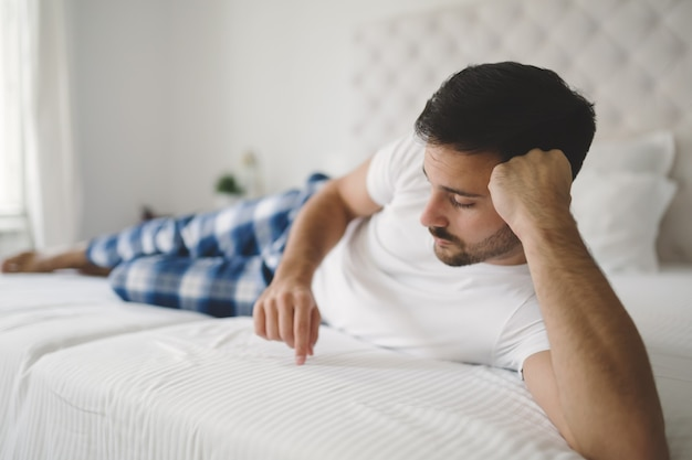 Załamany samotny mężczyzna w piżamie na łóżku