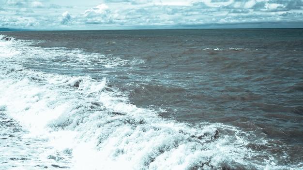 Załamująca się fala i wzburzone błękitne morze - format panoramy