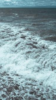 Załamująca się fala i wzburzone morze w formacie pionowej panoramy.