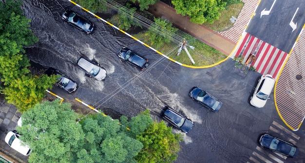 Zalana ulica po nienormalnej ulewie na przedmieściach. samochody poruszają się po zalanej ulicy. konsekwencje klęski żywiołowej.