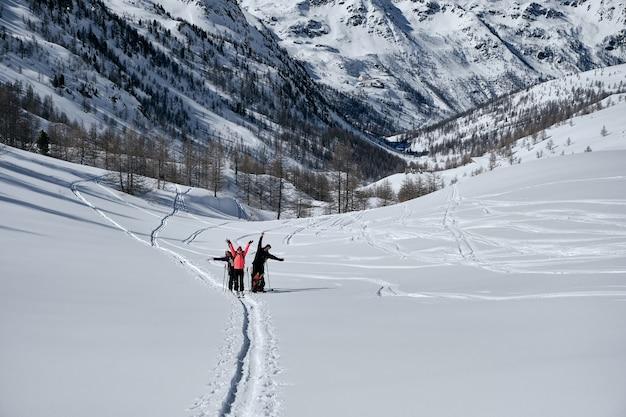 Zalesiona góra pokryta śniegiem i ludzie wędrujący w col de la lombarde