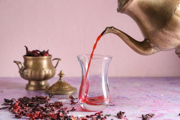 Zalewanie gorącej herbaty do tradycyjnego tureckiego kieliszka na stole