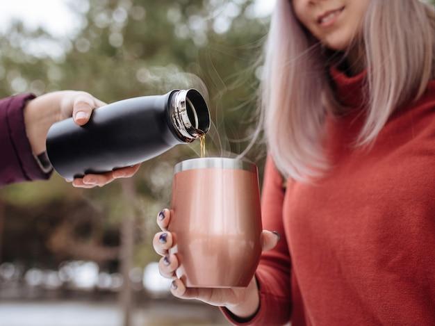 Zalewanie gorącej herbaty w termosie z zimowym lasem