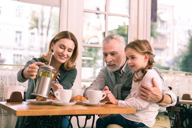 Zalewanie herbaty. rozpromieniona blond-włosa babcia nalewa herbatę swojej dziewczynie podczas śniadania w stołówce