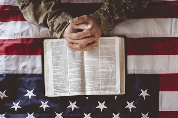 Żałobny i modlący się amerykański żołnierz z flagą amerykańską i biblią przed sobą