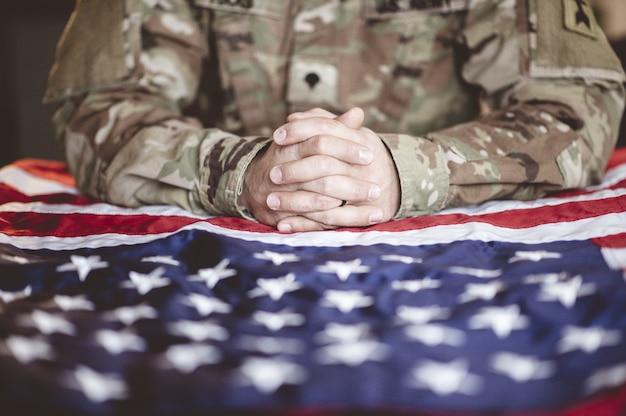 Żałobny i modlący się amerykański żołnierz z flagą amerykańską przed sobą