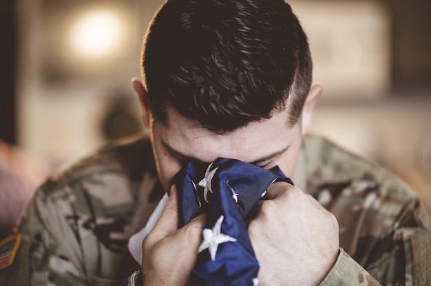 Żałobny i modlący się amerykański żołnierz z flagą amerykańską w dłoniach
