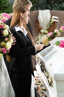 Żałobny mężczyzna i kobieta na pogrzebie z różową różą stojących przy trumnie lub trumnie