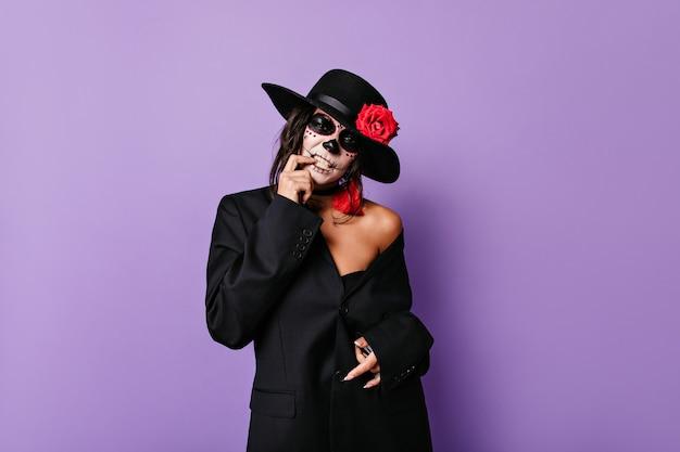 Żałosna mafioso kobieta w czarnym stroju dotyka zębów i pozuje w masce czaszki na liliowej ścianie na białym tle.